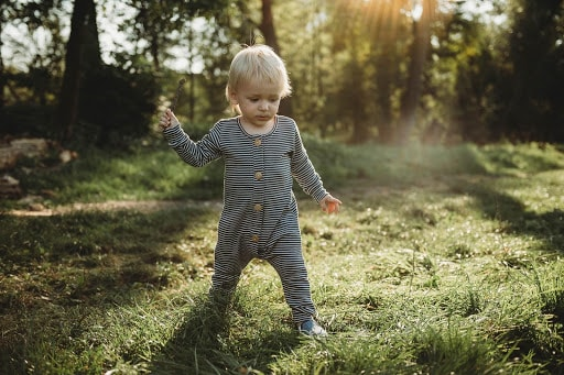 Baby in romper standing in meadow