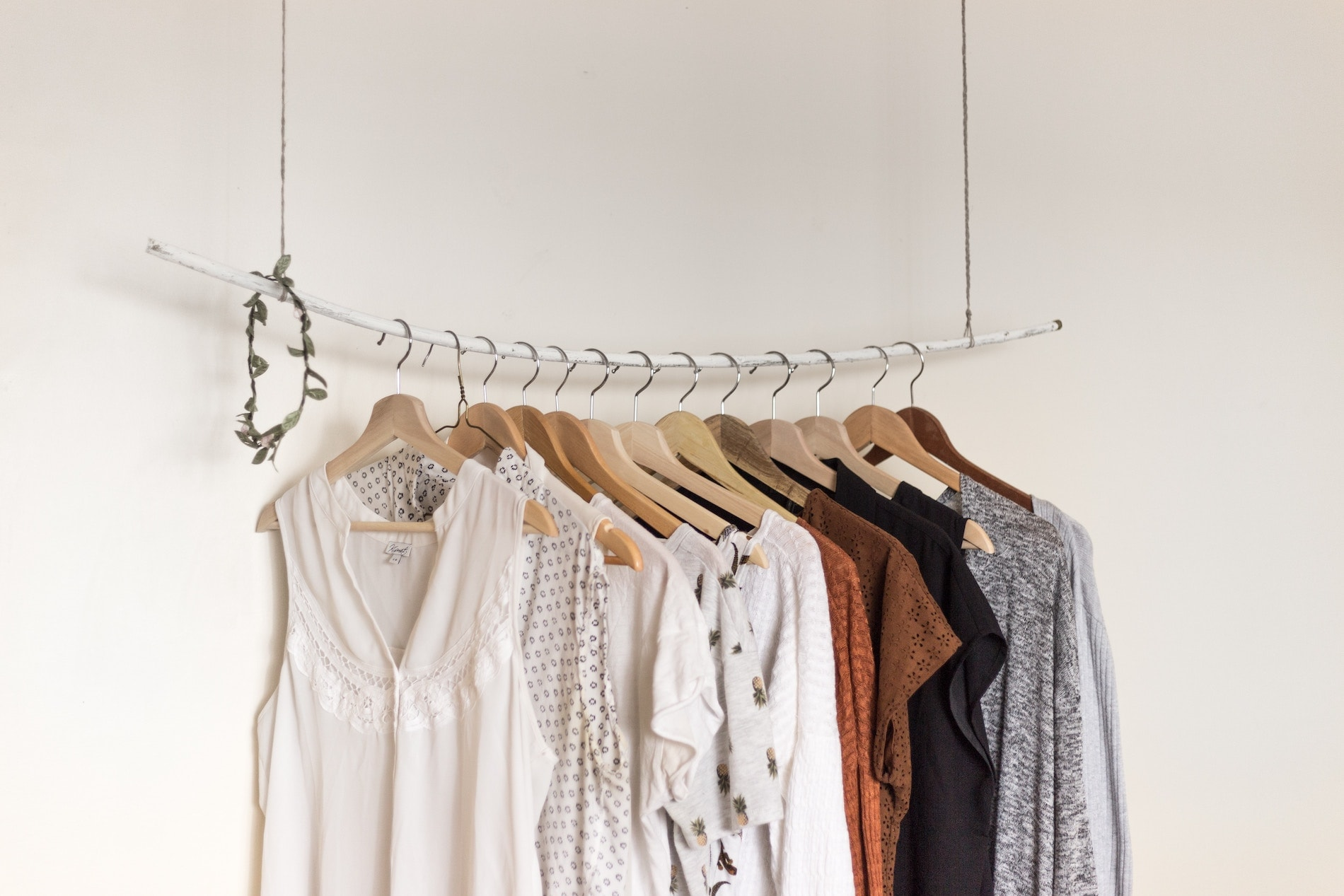 Capsule rack of garments hanging on a white wall